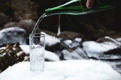 Kopalna woda mineralna nalewa od szklanej zielonej butelki w jasną szklaną zlewkę Zdjęcie Stock