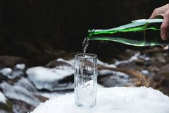 Kopalna woda mineralna nalewa od szklanej zielonej butelki w jasną szklaną zlewkę Fotografia Stock