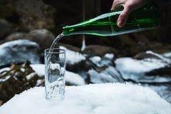 Kopalna woda mineralna nalewa od szklanej zielonej butelki w jasną szklaną zlewkę Obraz Royalty Free