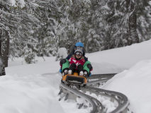 KOPAONIK, SÉRVIA - fevereiro, 05 Menino e menina que sledding no toboggan 5 de fevereiro de 2015 em Kopaonik, Sérvia Fotografia de Stock