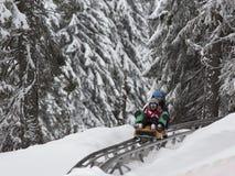 KOPAONIK, SERBIA - febrero, 05 Muchacho y muchacha sledding en el trineo largo 5 de febrero de 2015 en Kopaonik, Serbia Fotos de archivo