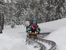KOPAONIK SERBIA, Luty, -, 05 Chłopiec i dziewczyna sledding na toboganie Luty 05, 2015 w Kopaonik, Serbia Fotografia Stock