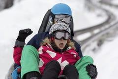 KOPAONIK SERBIEN - Februari, 05 Pojke och flicka som sledding på kälken Februari 05, 2015 i Kopaonik, Serbien Royaltyfria Foton