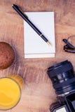Kopcake en drank met blocnote door camera op lijst Royalty-vrije Stock Foto's