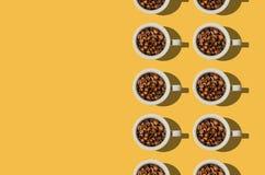 Kopconcept Witte koppen met koffiebonen op gele achtergrond Stock Afbeelding