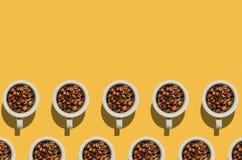 Kopconcept Witte koppen met koffiebonen op gele achtergrond Royalty-vrije Stock Foto's