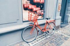 Kopenhagen, Denemarken 28 november, 2018 Uitstekende rode fiets dichtbij de grijze muur stock fotografie