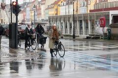 Kopenhagen - Oktober 23, 2016: Een oude dame en andere mensen op hun bycicles die de straat tijdens een regen in Nyhavn wachten t stock foto