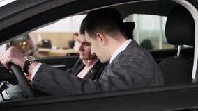 Koper die gesprek met autoverkoper hebben tijdens het inspecteren van de auto stock videobeelden