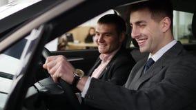 Koper die gesprek met autoverkoper hebben tijdens het inspecteren van de auto stock footage