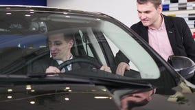 Koper die gesprek met autoverkoper hebben tijdens het inspecteren van de auto stock video