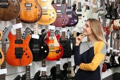 Koper die gitaar in muziekopslag kiezen royalty-vrije stock foto