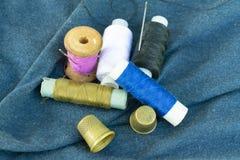 Koper oude vingerhoedjes, kleurrijke draden en naalden op blauwe stof stock afbeelding