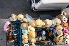 kopers De man probeert op glazen, vrouwenhulp die de spiegel voor hem houden Zij zijn dichtbij lijst met hoeden en glazen op de s royalty-vrije stock afbeeldingen