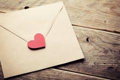 Koperta, list lub czerwieni serce na nieociosanym drewnianym stole dla miłości wiadomości na walentynka dniu w retro tonowaniu zdjęcia royalty free
