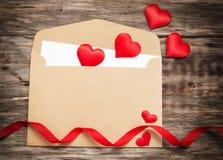 Koperta z czerwonymi tkanin sercami Fotografia Stock
