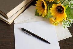 Koperta z listem na drewnianym stole Książki, pióro i kwiaty, Zdjęcie Royalty Free