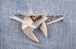 Kopf des Zangenschwarz-Griffwerkzeugs durchbohren durch alte Blue Jeans b Lizenzfreie Stockfotos