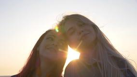 Kopf-an-Kopf- Lächeln von zwei Freunden gegen den Sonnenuntergang über dem Meer stock footage