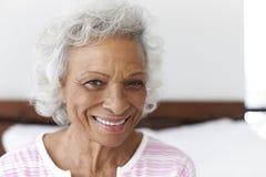 Kopf und Schulter-Porträt der lächelnden älteren Frau, die zu Hause auf dem Bett schaut positiv sitzt stockfotos