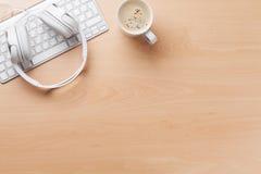 Kopfhörer über Tastatur und Kaffeetasse Stockfotos