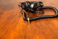 Kopfhörer auf der braunen Tabelle Stockbilder