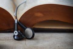 Kopfhörer auf einem geöffneten Buch Lizenzfreies Stockbild