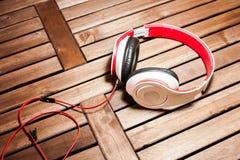 Kopfhörer auf hölzerner Latte lizenzfreie stockfotos