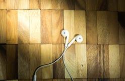 Kopfhörer auf Holz Lizenzfreies Stockfoto