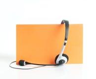 Kopfhörer auf orange Hintergrund Lizenzfreie Stockfotografie