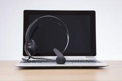 Kopfhörer, der auf einem offenen Laptop balanciert Stockfotografie