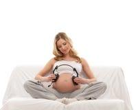 Kopfhörer einer junge blonde der schwangeren Frau Holding Stockfoto