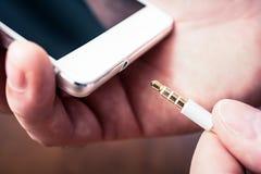 Kopfhörer Jack Of, den ein Weiß Smartphone einem weißen Kopfhörer-Kabel angeschlossen erhält stockfotografie