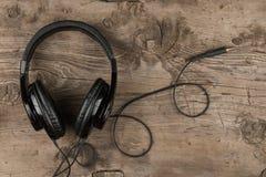 Kopfhörer liegt auf hölzerner Schreibtischtabelle Abbildung der elektrischen Gitarre Lizenzfreies Stockfoto