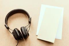 Kopfhörer mit Anmerkung des braunen und Weißbuches über hölzernen Schreibtisch Lizenzfreies Stockbild