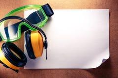 Kopfhörer, Schutzbrillen und leeres Papier Stockbild