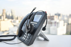 Kopfhörer und das IP-Telefon Lizenzfreies Stockfoto
