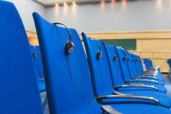 Kopfhörer und Empfänger auf den Stühlen Lizenzfreies Stockbild