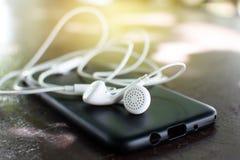 Kopfhörer und Kasten des intelligenten Telefons mit weichem Licht Stockfotografie