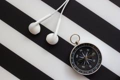 Kopfhörer und Kompass auf Schwarzweiss-Hintergrund, Konzeptreise mit Musik Stockfotos