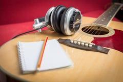 Kopfhörer und Notizbuch und Bleistift auf Gitarre Lizenzfreie Stockbilder