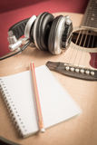 Kopfhörer und Notizbuch und Bleistift auf Gitarre Stockfotos