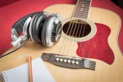 Kopfhörer und Notizbuch und Bleistift auf Gitarre Stockfoto