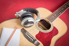 Kopfhörer und Notizbuch und Bleistift auf Gitarre Lizenzfreie Stockfotografie