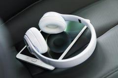 Kopfhörer und Tablet-Computer auf dem Autositz Lizenzfreies Stockfoto
