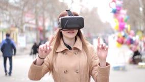 Kopfhörergläser junges Mädchen tragende vr virtueller Realität, die den Spaß spielt draußen in der Straße in beige outwer Mantel  stock footage