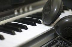 Kopfhörer auf Tastatur Stockbild