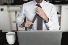 Kopfloser Mann, der Bindung am Schreibtisch justiert Stockfotos