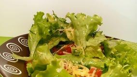 Kopfsalat, der auf eine Platte von nährenden Tomaten des Käses spinnt stock footage