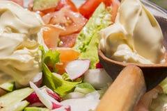 Kopfsalat, Gurken, Tomaten, Rettiche und Majonäse Stockfotografie